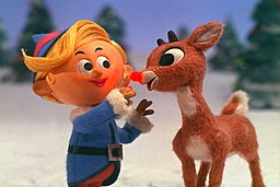 The image is a photo of the television show Rudolph the Red Nosed Reindeer. It shows Hermie the Elf touching the glowing nose of Rudolph as they sing together.