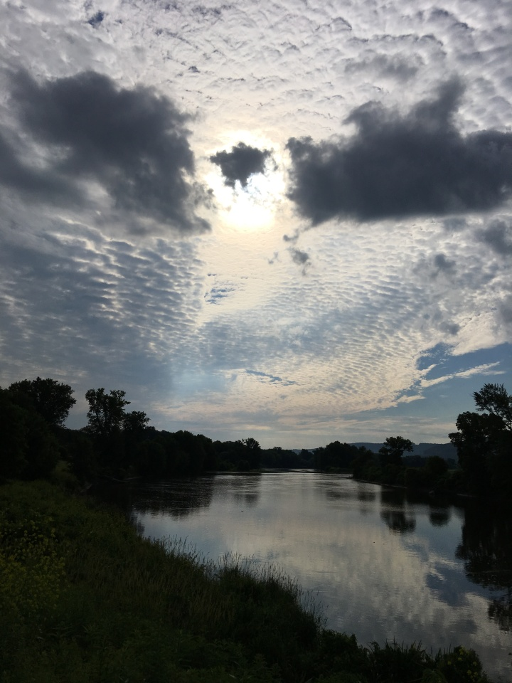 A river with trees on both sides. The sun is partially hidden behind clouds and is reflected in the placid river.