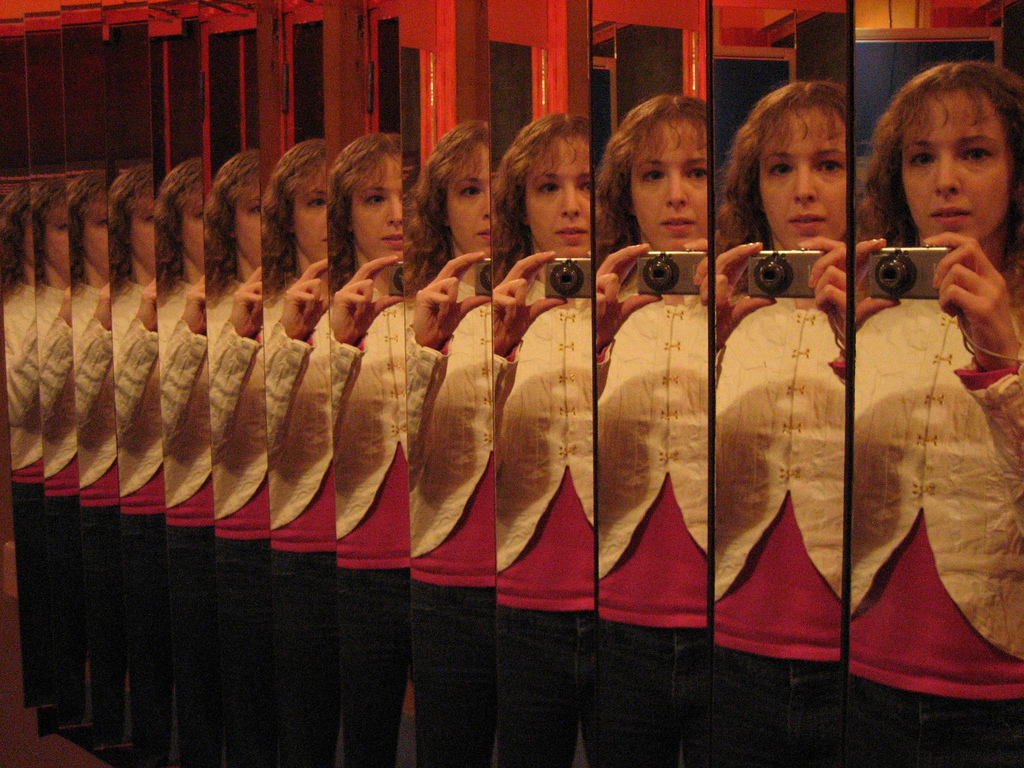 Woman's image is repeated over and over in an infinity mirror
